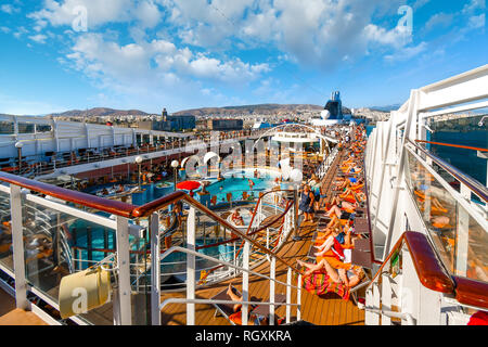 Athens, Greece - September 18 2018: Tourists lounge in the sun, swim and party on the upper deck of a large cruise ship as it leaves port of Athens - Stock Image