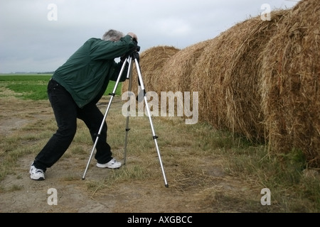 A photographer with tripod creating a picture of bales of hay. - Stock Image