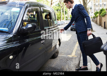 Young businessman reaching to open the door of a London taxi - Stock Image
