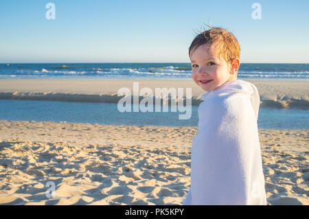 Smiling little boy wrapped in a towel after swiming. Sunset shot - Stock Image