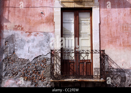 A small door with iron balcony against a red crumbling wall in Sicily, Italy - Stock Image