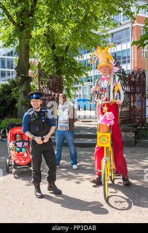 Childrens Entertainer with PCSO and black father and baby. - Stock Image