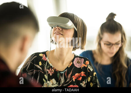 Woman using VR goggles in office - Stock Image