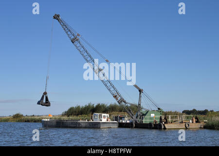 The Broads Authority using an excavator crane to dredge the River Bure on the Norfolk Broads - Stock Image