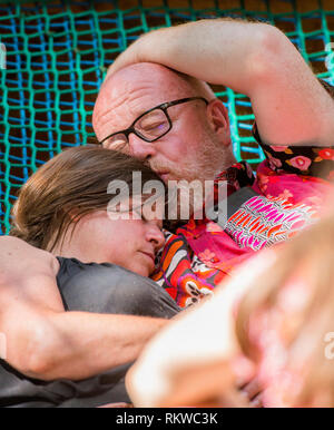 A couple asleep in the shade and cuddling each other at Latitude Festival 2018. - Stock Image