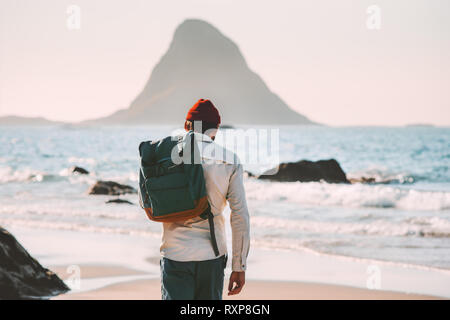 Man with backpack walking on empty beach traveling lifestyle vacations in Norway outdoor solitude emotions - Stock Image