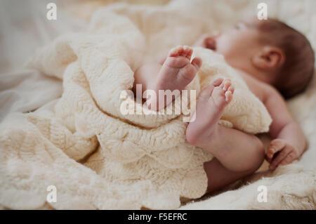 Sleeping baby lying on bed - Stock Image