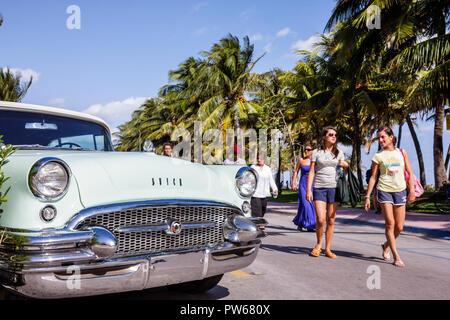 Miami Beach Florida Ocean Drive New Year's Day Art Deco District pedestrian woman man palm tree stroll walk Buick 1950's class - Stock Image