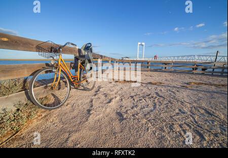 Bike with Child Bike Carrier parked beside Tavira Island pedestrian drawbridge, Barril Beach, Algarve, Portugal - Stock Image