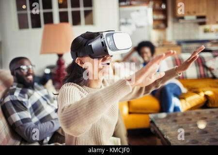 Woman gesturing, using virtual reality simulator glasses in living room - Stock Image