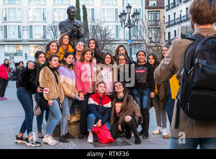 Madrid Plaza de Santa Ana Group of young female students posing with statue of Spanish poet and playwright Federico Garcia Lorca - Stock Image