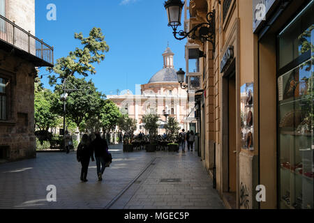 Street scene, North Cuitat Vella district, with landmark building Basilica de los Desamparados in Plaza de la Virgen, Valencia, Spain - Stock Image