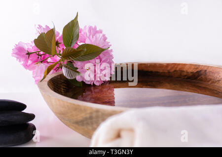 Wooden bowl with water and pink flower and black rock and towel isolated on white background. Natural organic cosmetic, wellness and spa concept - Stock Image