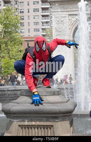 A street artist performer dressed as SPIDERMAN poses for photos and solicits contributions. In Washington Square Park, Manhattan, New York City. - Stock Image