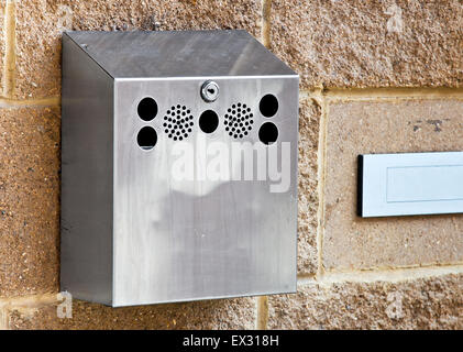 Wallmounted stainless steel cigarette bin on an exterior wall outside a place of work where smoking is banned inside. - Stock Image