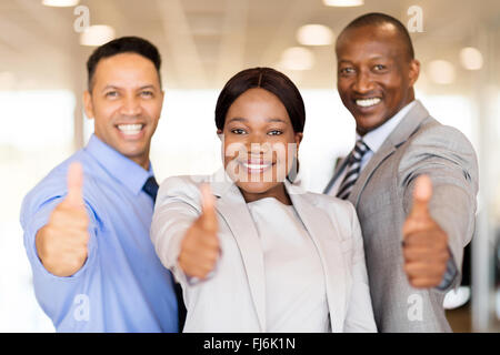 portrait of beautiful car dealership staff giving thumbs up - Stock Image