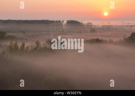 The village near the forest completely covered in mist at dawn with the rising sun over the horizon - Stock Image