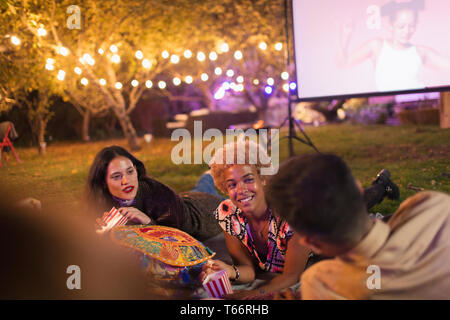 Friends hanging out, watching movie in backyard - Stock Image