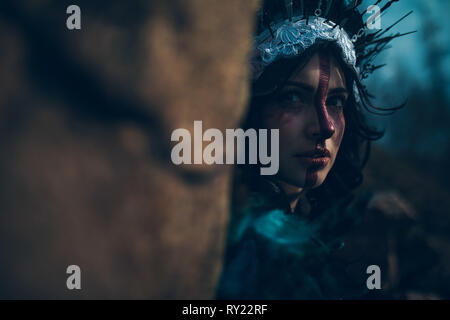 Portrait of young woman in the image of a fairy and a sorceress standing next to the rock in a black dress and a crown. - Stock Image