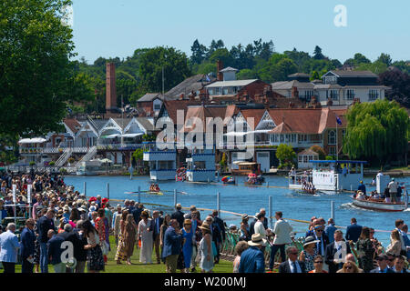 Henley on Thames, Berkshire, UK. 4th July, 2019. Henley Royal Regatta. Viewing the race from the Regatta  Enclosure with crowds in the Stewards Enclosure and Henley's  town behind, Credit Gary Blake/Alamy Live - Stock Image