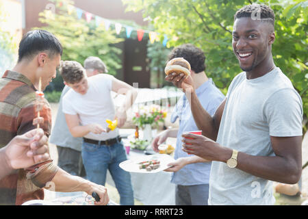 Portrait smiling young man enjoying barbecue with friends - Stock Image