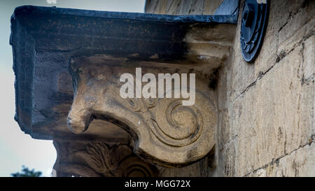 Hand carved limestone horse's head corbel add architectural decoration and structural support to a porch in the ancient town of Chipping Campden - Stock Image