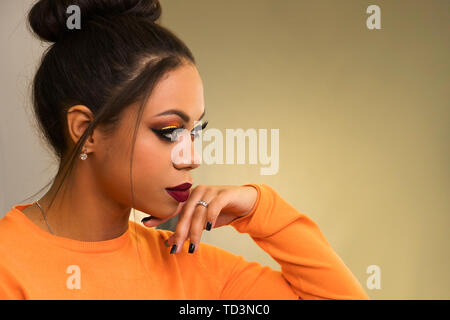 Portrait of attractive afro american young woman with fashion luxury makeup orange-coloured shades and her hair scraped back into high bun. - Stock Image