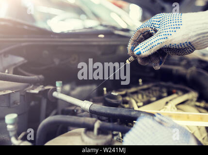 mechanic with dipstick checking motor oil level - Stock Image