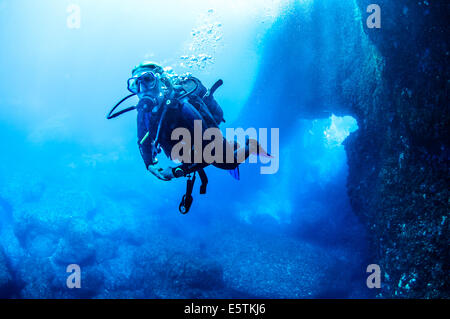Young female diver swimming out of the blue hole in gozo against a deep blue sea - Stock Image