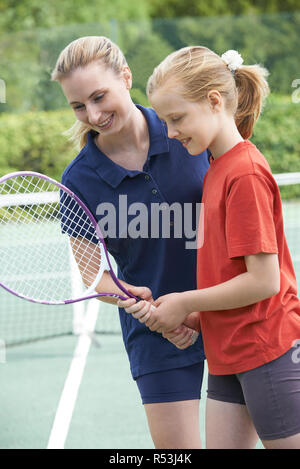 Female Tennis Coach Giving Lesson To Girl - Stock Image