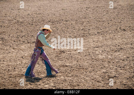 Rodeo Cowboy walking across the dirt arena. - Stock Image