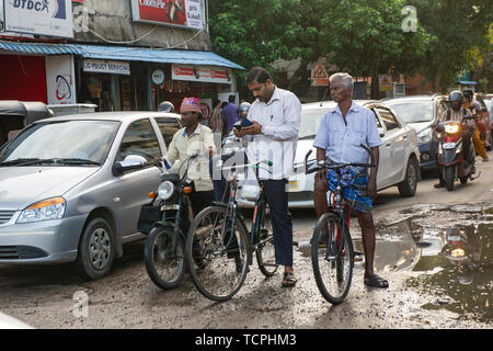 Poverty in Chennai, India, where cyclists wait at a junction, one looking at his smartphone - Stock Image