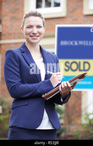 Portrait Of Female Realtor Standing Outside Residential Property - Stock Image
