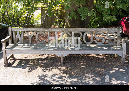 Ornate long wooden garden bench seat with carved lettering at Wych Cross Garden Centre, East Sussex, England, UK - Stock Image