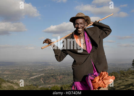 A maasai man smiling on a hill with view of Kenya in background. - Stock Image