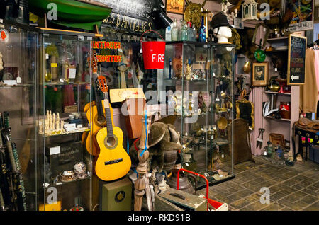 An antique shop and bric a brac shop with a selection of vintage and reproduction musical instruments clothing and war-time items in the Shambles cove - Stock Image