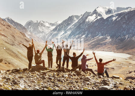 Big happy active company of friends sits in mountains and having fun with raised arms - Stock Image
