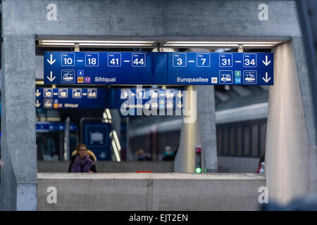 Direction signs guide and inform travelers on the platforms of Zurich main station. - Stock Image