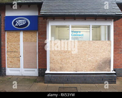 Ashbourne Shrovetide Football 2019. Shops boarded up prior to Ash Wednesday match including branch of Boots chemist advertising Viagra. - Stock Image