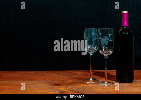 Beautiful etched wine glasses and bottle of red wine on wooden table and dark background. Valentines, Mothers Day, Easter, Christmas, Wedding Concepts - Stock Image