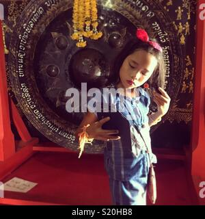 Laotian girl taking a selfie photo of herself in a temple in Luang Prabang - Stock Image