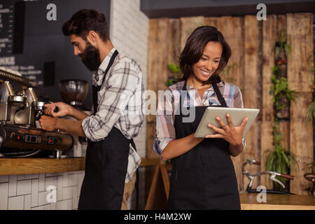 Waitress using digital tablet while waiter preparing coffee in background - Stock Image