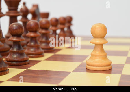 White pawn in front of the black lining - Stock Image