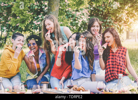 Happy girls eating watermelon at picnic dinner in the garden - Young women having fun enjoying lunch together in the backyard - Stock Image