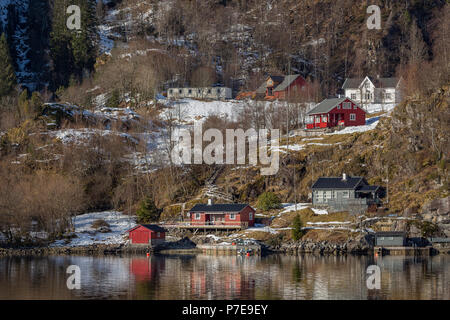 Village built on the shoreline of Osterfjorden, Norway. Taken from the Bergen to Mostraumen cruise. - Stock Image
