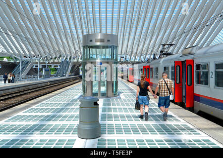 Back view of young man & woman couple holding hands walking along long train station platform in Liège Belgium modern railway building summer day EU - Stock Image