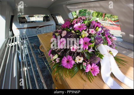 A coffin with a flower arrangement in a funeral car - Stock Image