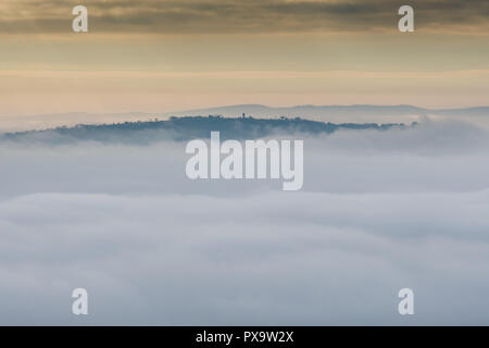 Flounders Folly rising above the mist in Ape Dale, seen from Ragleth Hill, Church Stretton, Shropshire - Stock Image