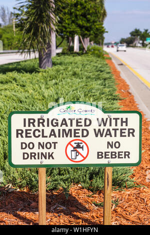 Naples Florida US Route 41 Tamiami Trail road car median landscaping sign irrigated with reclaimed water bilingual sign Spanish - Stock Image