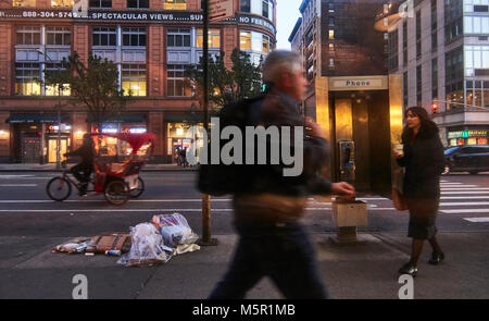 People walking by a dirty 6ath avenue in Manhattan, avoiding garbage on the floor - Stock Image